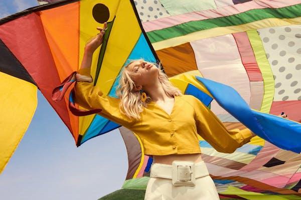 blonde female model flying a colourful kite, feeling her oats
