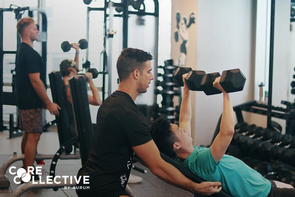 caucasian male fitness instructor guiding asian male client