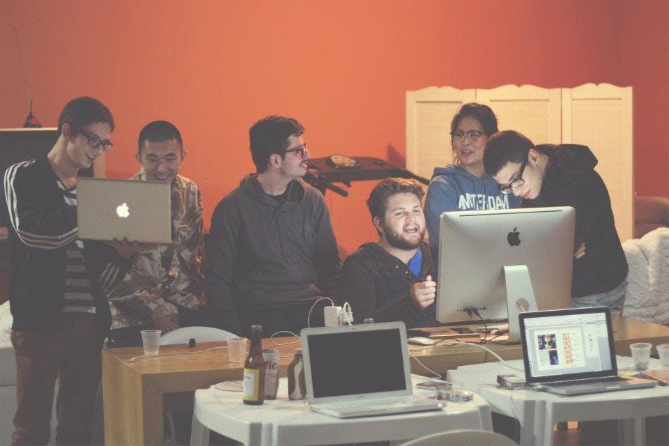 Imagem com pessoas sentadas olhando para um computador.