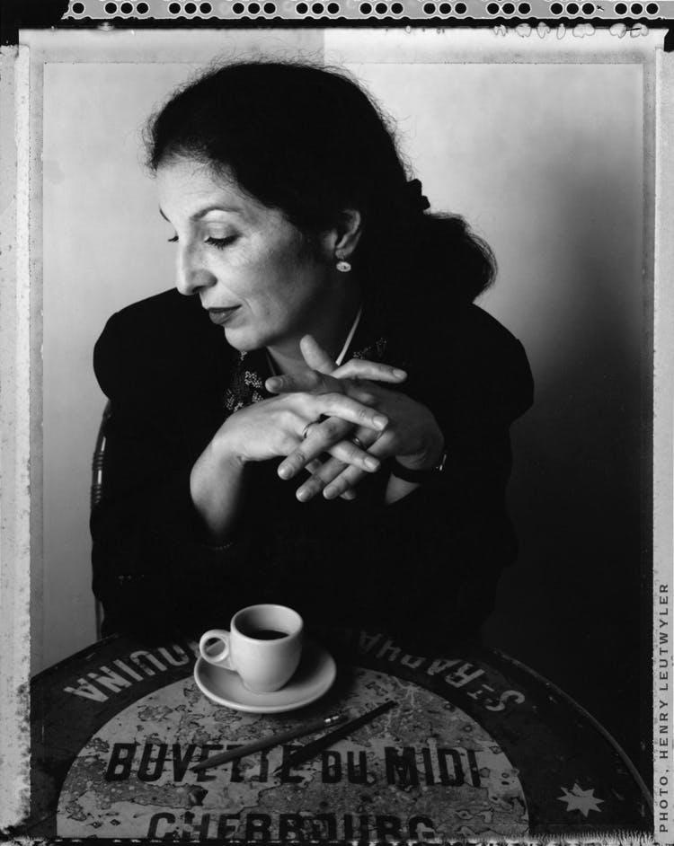 Fotografia de Louise Fili, em preto e branco, sentada, tomando café.