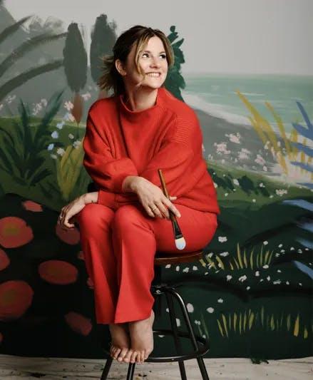 Fotografia de Anna Bond, sentada numa cadeira, vestida de vermelho. Ao fundo, uma paisagem pintada.