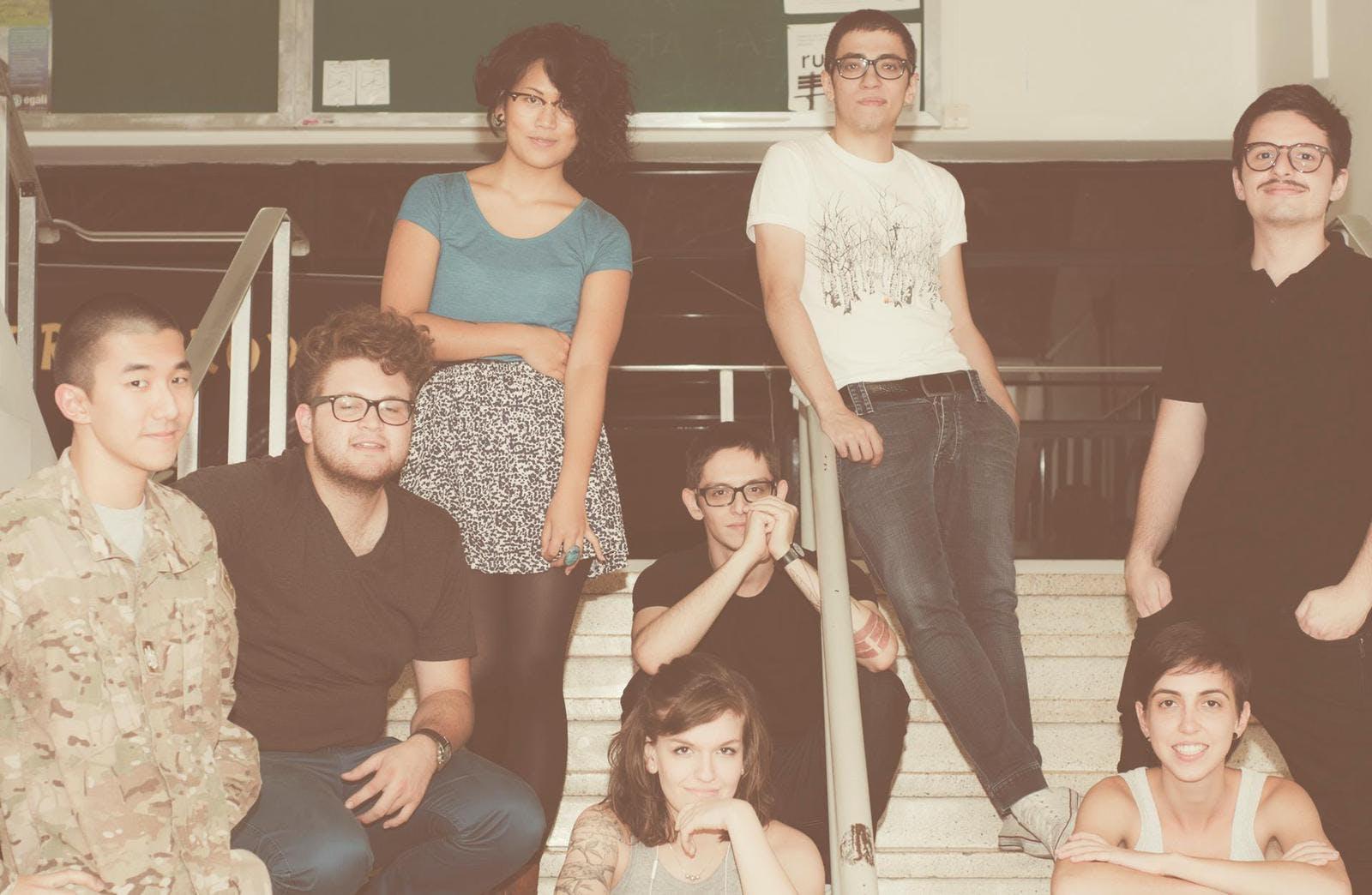 Imagem com oito pessoas numa escada. Algumas estão sentadas e outras em pé.