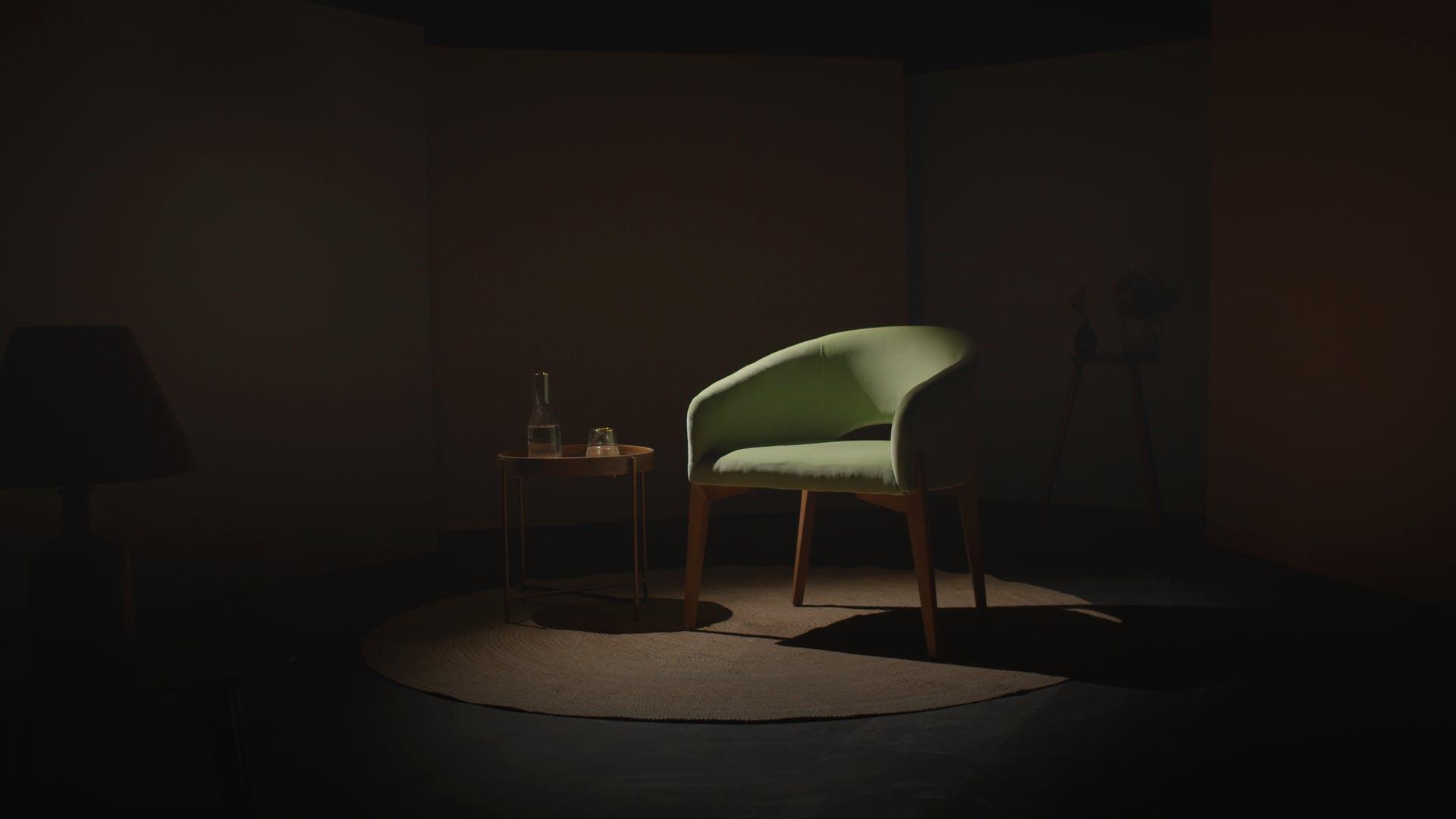 Silla verde en medio de una habitación oscura.