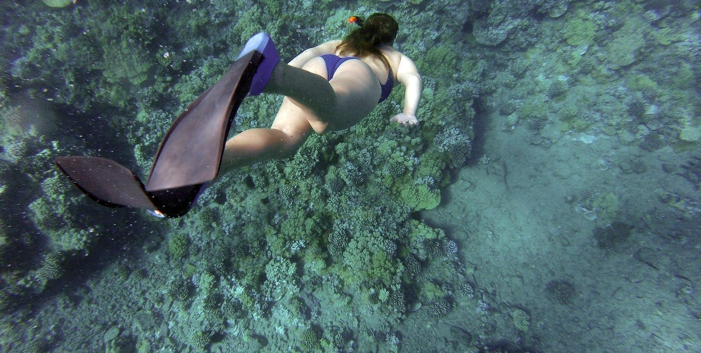 En kvinne som snorkler i havet