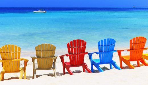 Blått hav med fargerike solstoler på stranden