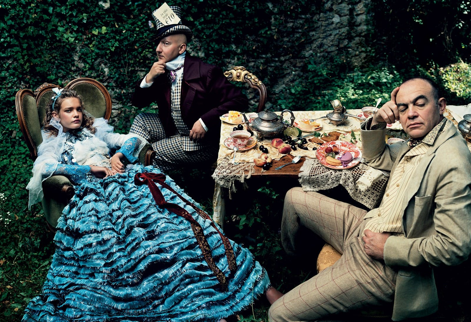 "Natalia Vodianova as Alice, in a ""Christian Lacroix Haute Couture dress with painted and sculpted mink dikey over a lace top and frilled lamé skirt. Stephen Jones (left) wears a custom-made hat of his own design. Lacroix, as the March Hare, is at far right."" Annie Leibovitz, Vogue, 2003"