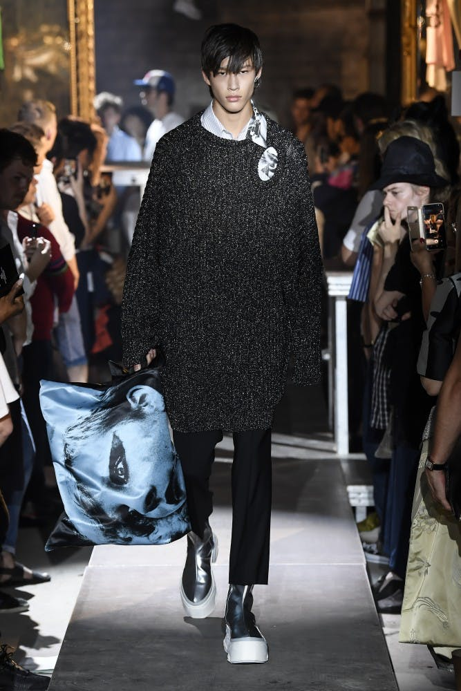 raf simons runway show ss19 grey oversized sweater black slim trousers blue eastpak collaboration poster tote