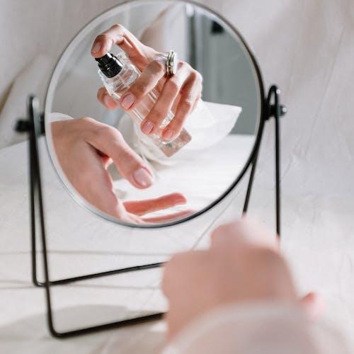 Espelho mostrando uma pessoa passando perfume no pulso
