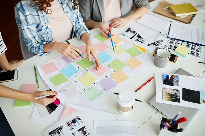 Three people brainstorming ideas using multicoloured sticky notes on a large piece of paper.