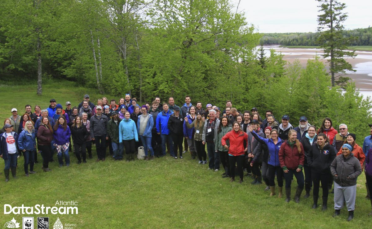 Group of Atlantic Canadian community based water monitoring groups standing for a photo on a field next to a river