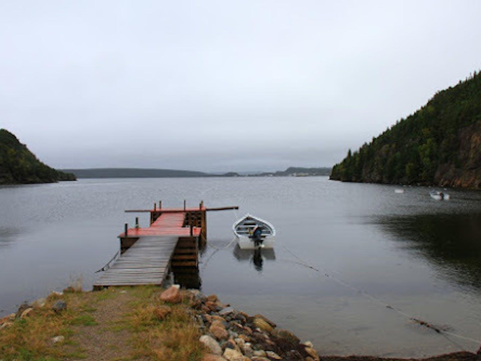 une scène d'un lac avec un quai à moitié peint en rouge au milieu s'étendant dans l'eau. Un bateau est attaché au quai et entouré de montagnes.