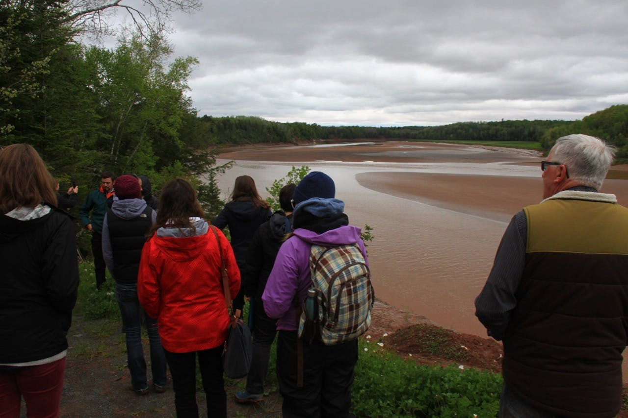 Kickoff attendees descend the embankment towards the Shubenacadie River during the Day Two Water Monitoring Field Trip. Photo: Oliver Woods.