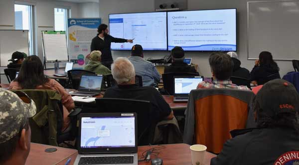 Data Specialist Patrick LeClair at the front of the room pointing to the screen as he does a Datathon in Yellowknife