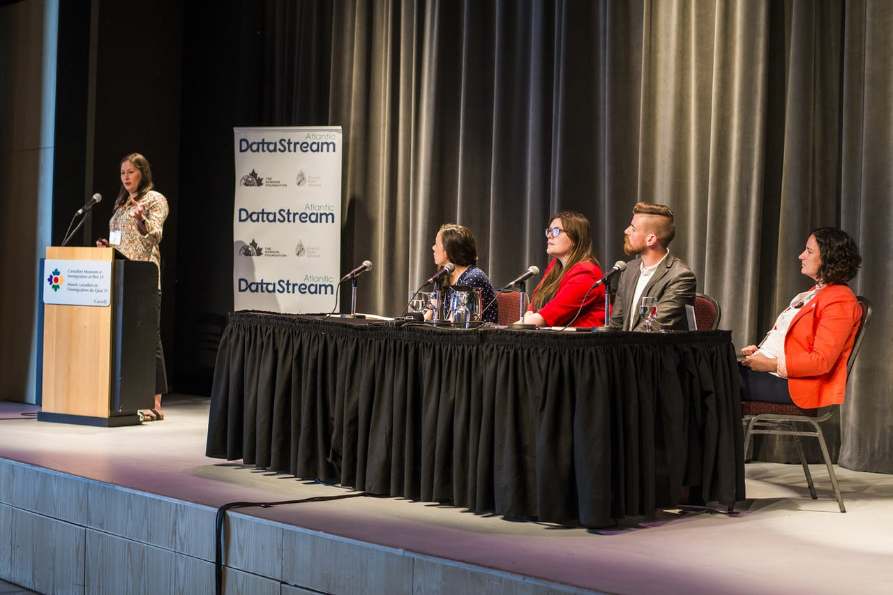 Gila Somers standing at a podium speaking while Carolyn DuBois, Emma Wattie, Graeme Stewart-Robertson, and Elizabeth Hendriks sit at a table on stage