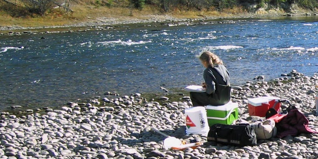 Woman sitting on a cooler next to a river recording water quality results onto a field sheet