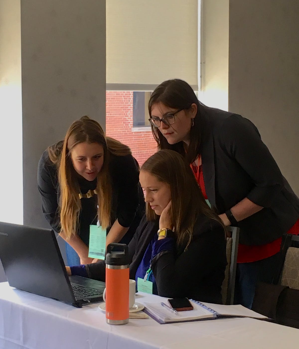 Chelsea Lobson, Emma Wattie, and Keila Miller looking at Atlantic DataStream on a laptop during a datathon