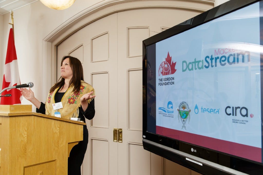 Lana Lowe at a podium next to a screen displaying logos for the gordon foundation, mackenzie datastream, the government of the northwest territories, Fortn Nelson First Nation, Tesera, and CIRA