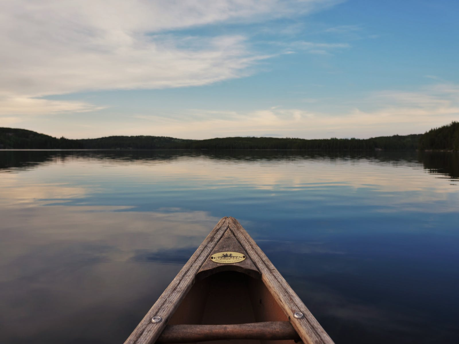 canoe centered on the water surrounded by tree line