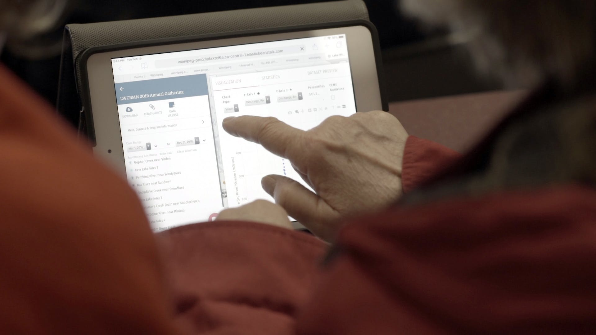 hand of an elderly person pointing at a tablet displaying a datastream visualization page