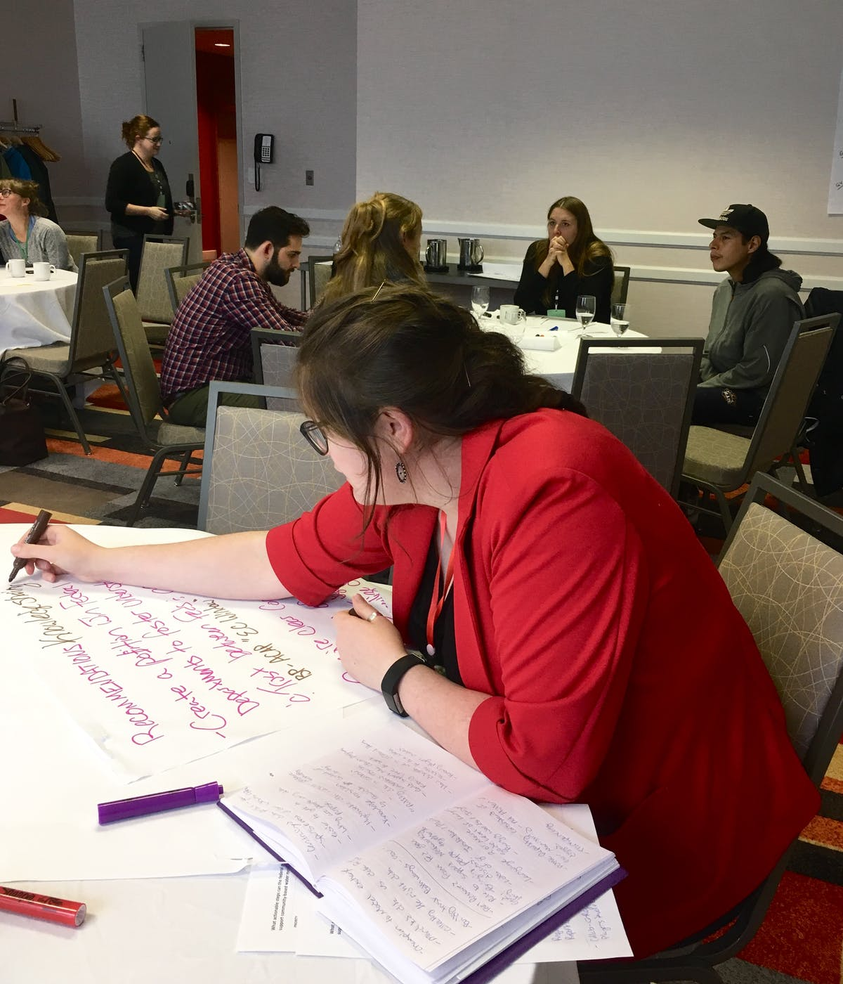 Emma Wattie writing notes at a mini roundtable