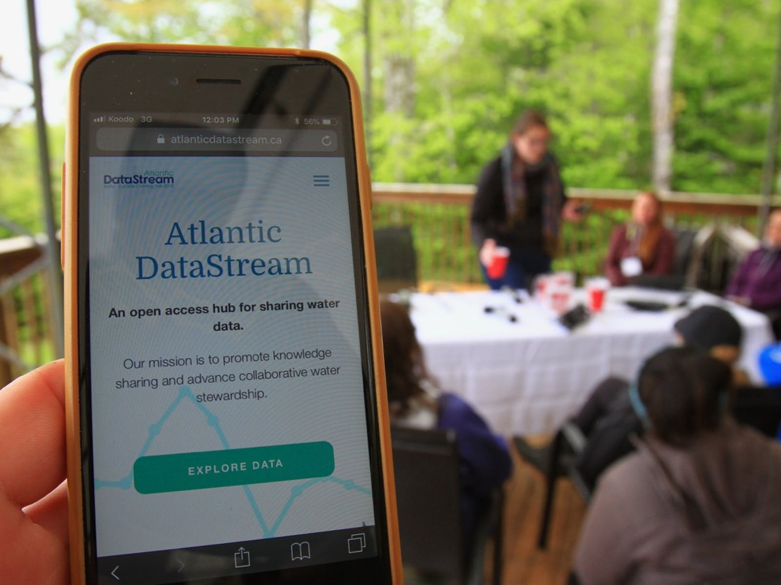 Iphone displaying the Atlantic DataStream homepage with people on a deck around a table in the background