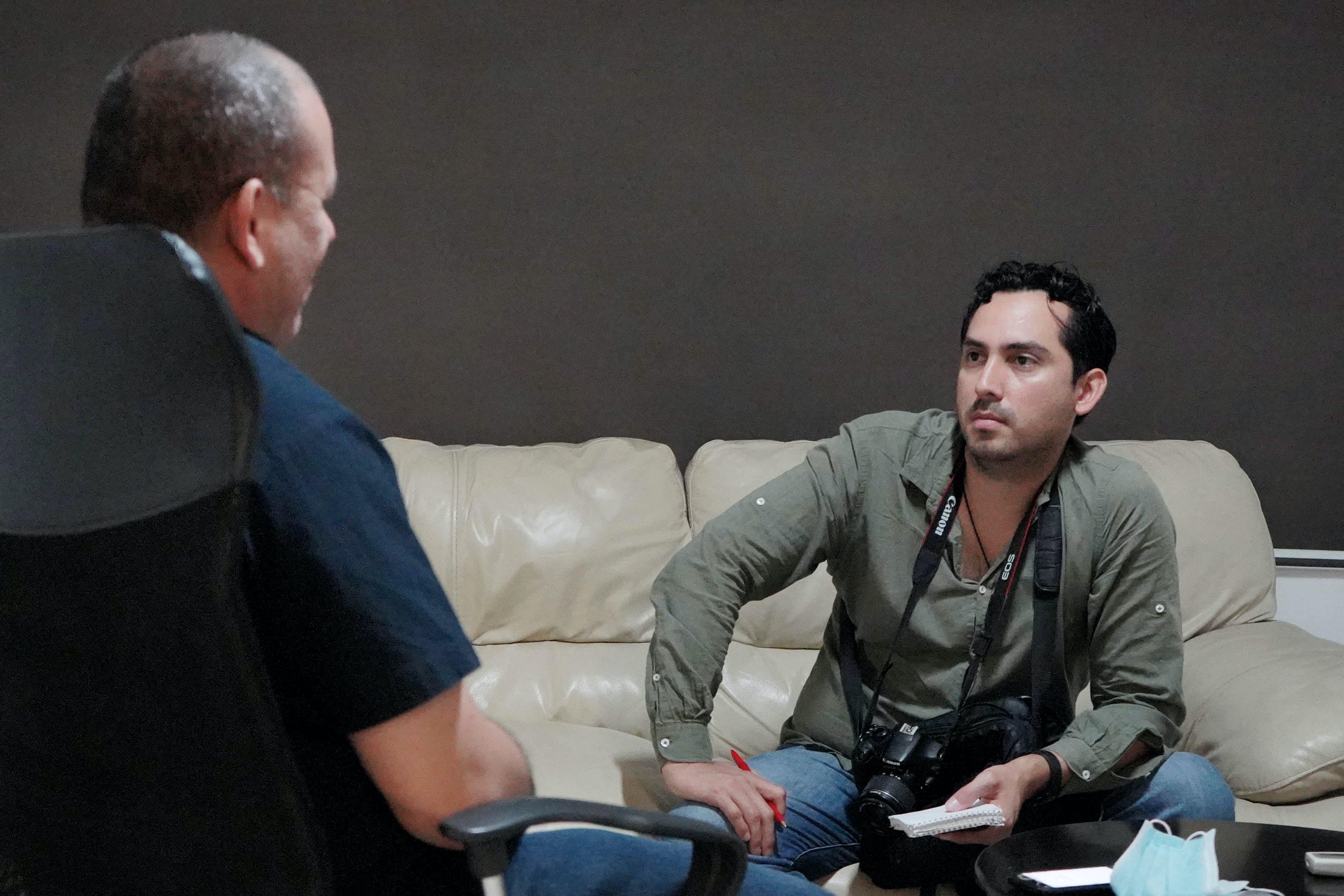 periodista entrevista a una persona en los interiores de una casa