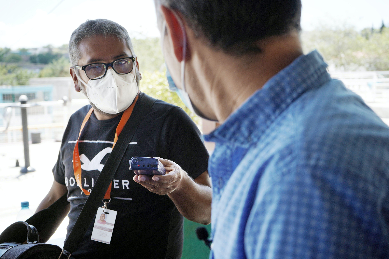 periodista entrevista a una persona con su grabadora en la mano
