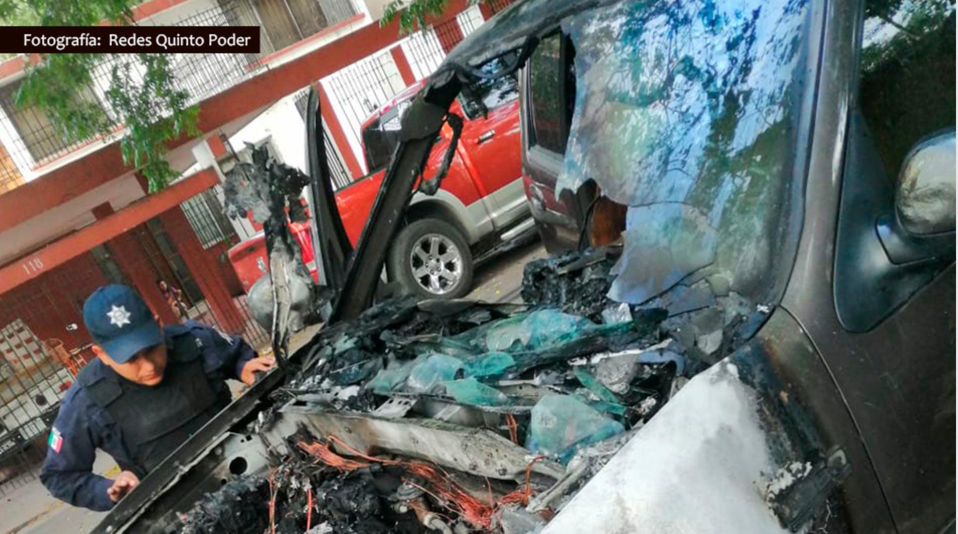 policia revisa un auto incendiado.