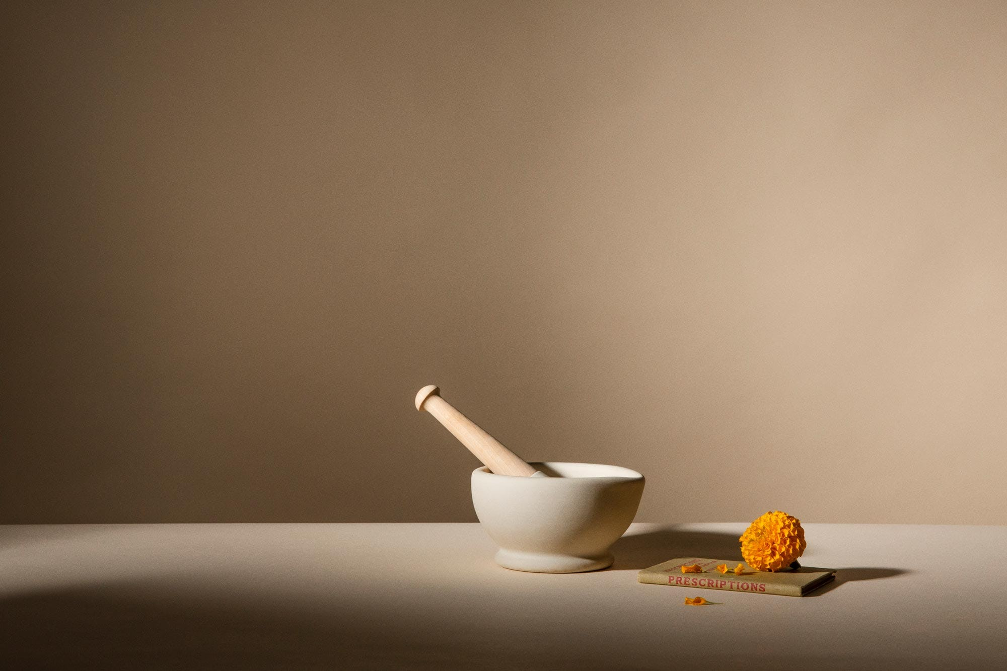 Pestle and mortar next to a flower