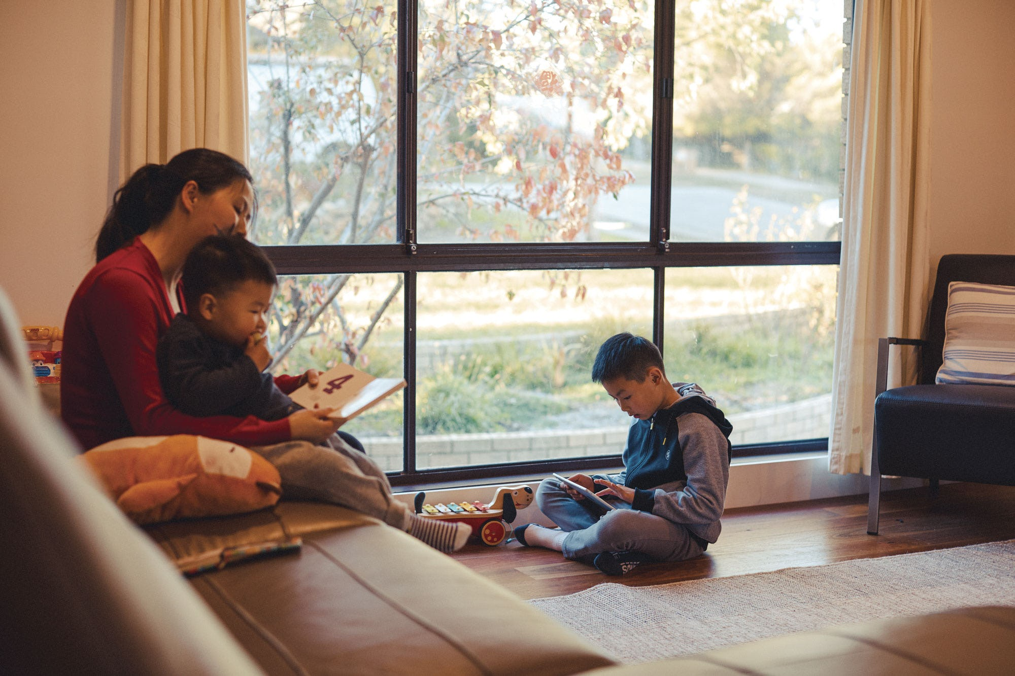 A family sitting in a living room accessing the Library's digital archives on a tablet