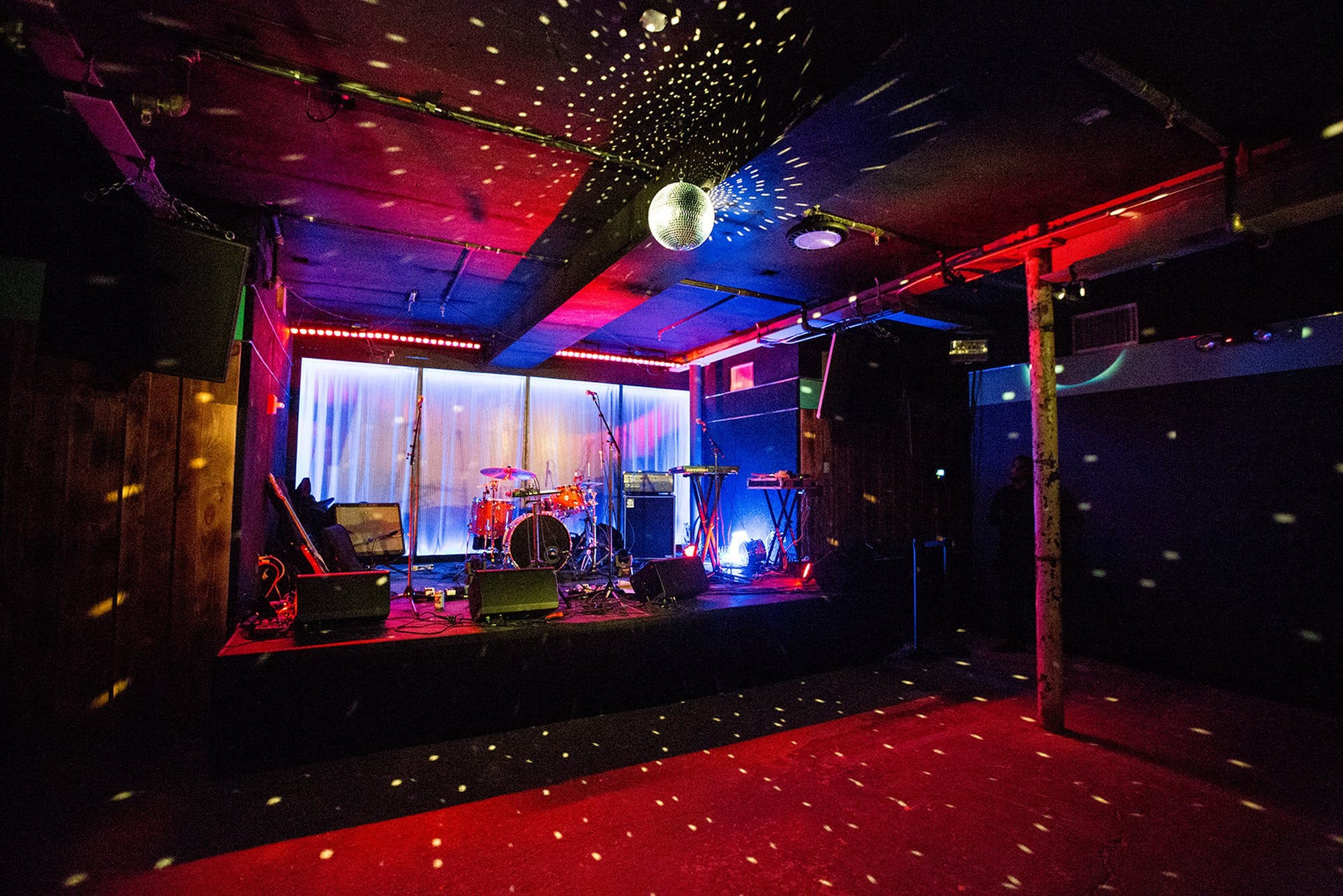 A room at the venue Elsewhere with instruments set up on stage and a disco ball shining