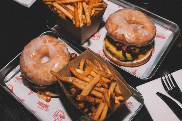 donut burgers with fries and sauce on a table