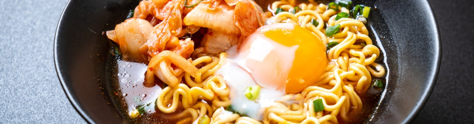 spicy noodles with kimchi and a poached egg