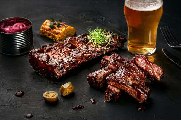Slow-cooked ribs being served at a restaurant with a beer