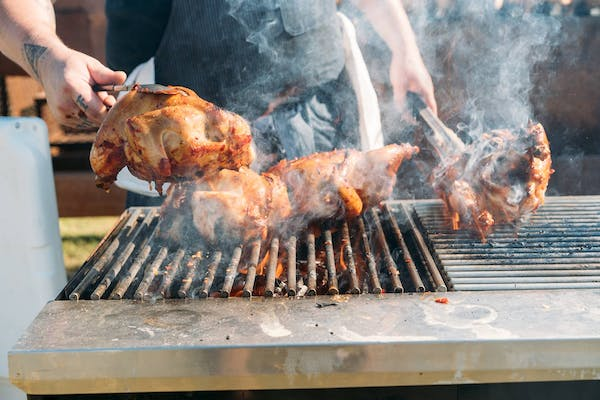 chickens being roasted on a grill
