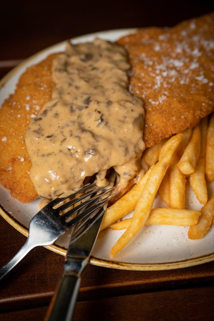 The Golden-Crumbed Chicken Schnitzel with mushroom sauce and fries