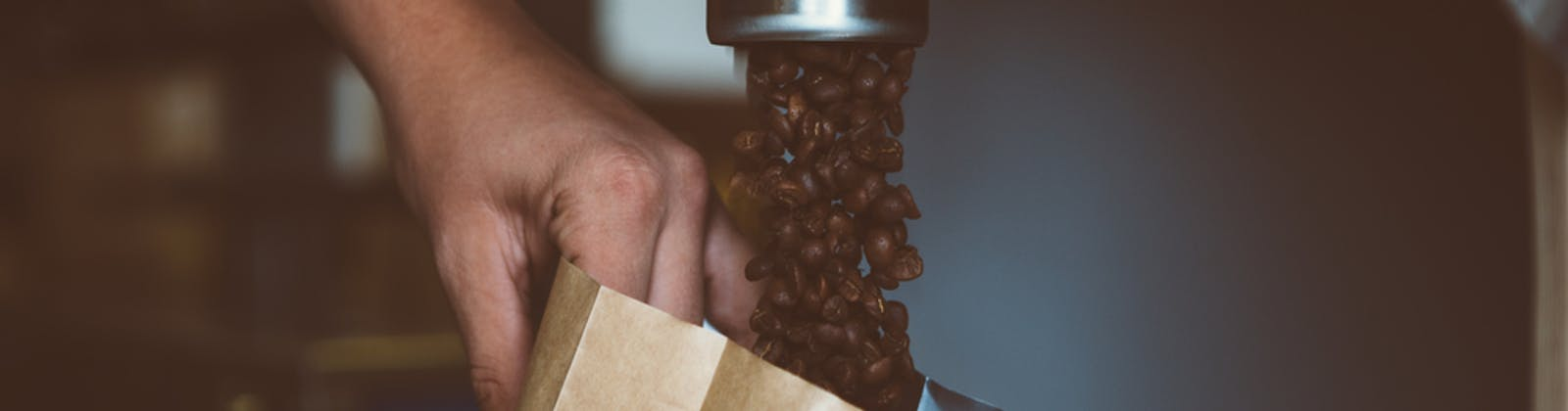 coffee beans pouring into a bag