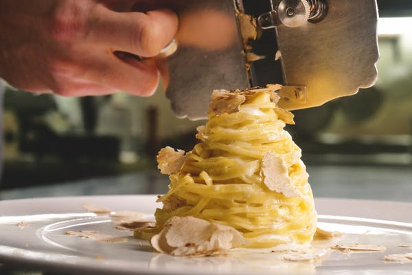 truffle being shaved onto egg pasta