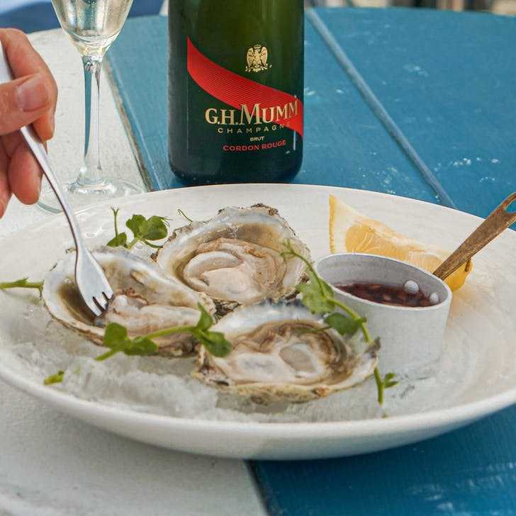 Enjoy freshly shucked oysters by the sea.
