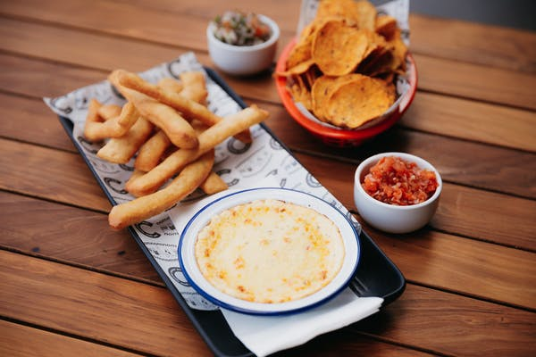 cheese fondue with breadsticks corn chips and salsa