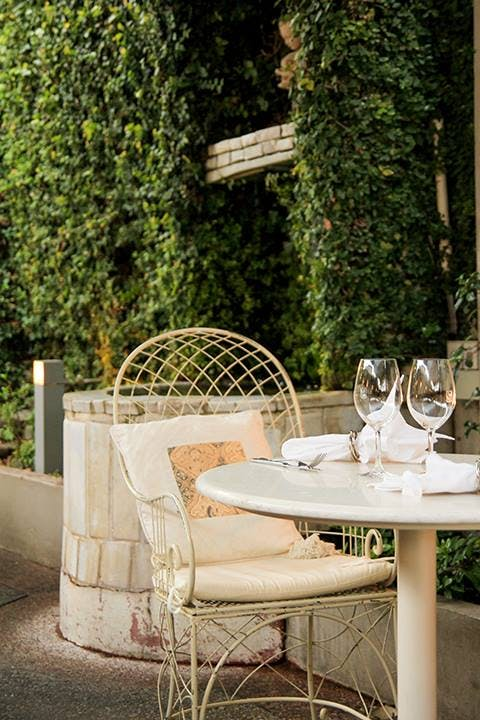 Non Solo Pizza's wrought iron chairs and lush greenery