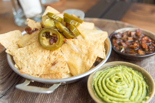 nachos with chilli, guacamole, and jalapenos