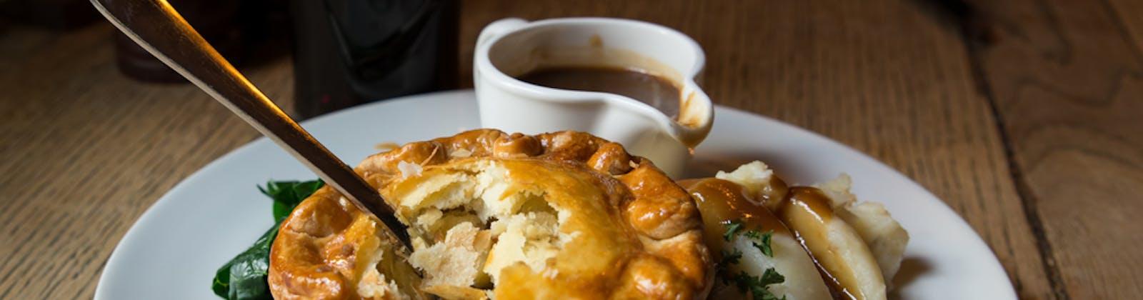Pub pie with potato mash and greens