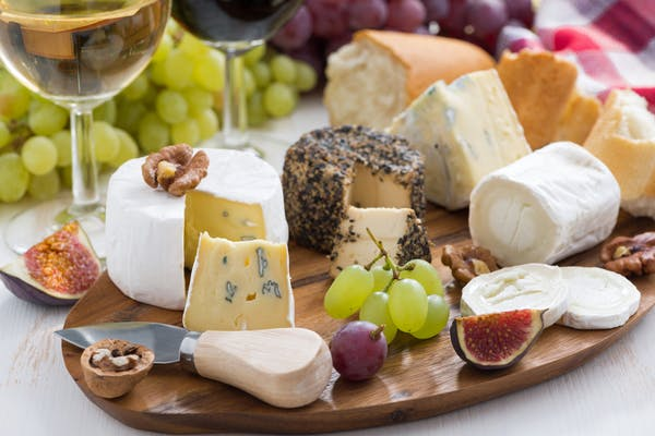 a cheese board platter with dine and fruit and bread
