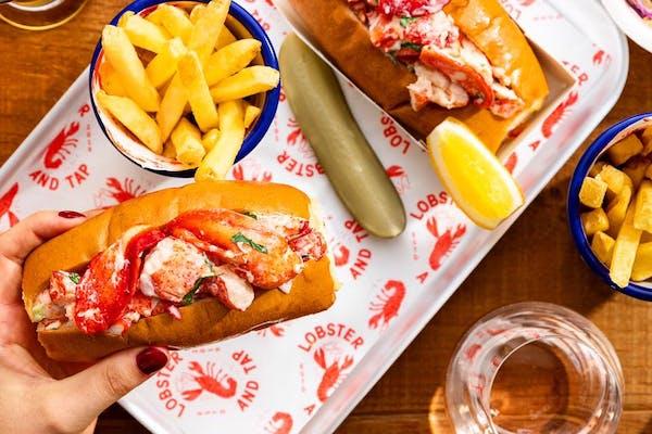 lobster rolls, pickles, chips, and lemon wedge