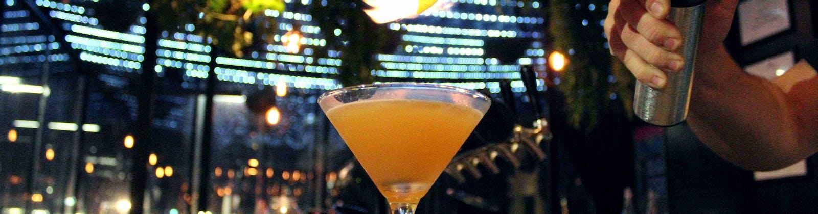 bartender toasting orange peel for a margarita