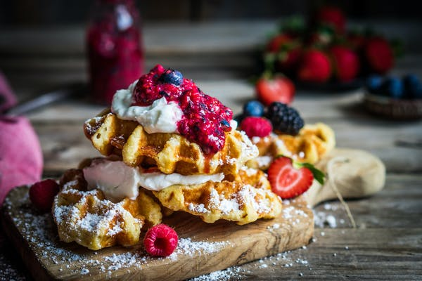 waffles on board with berries and cream
