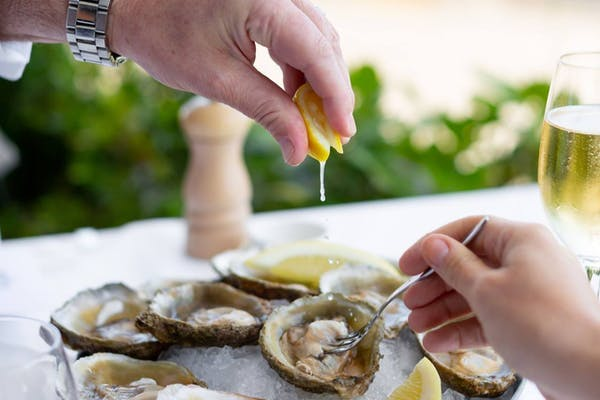 Lemon being drizzled on oysters