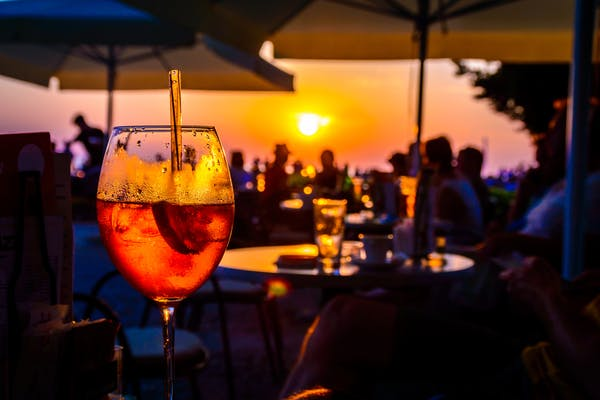 Wine glass on table in a restaurant against a setting sun in the background