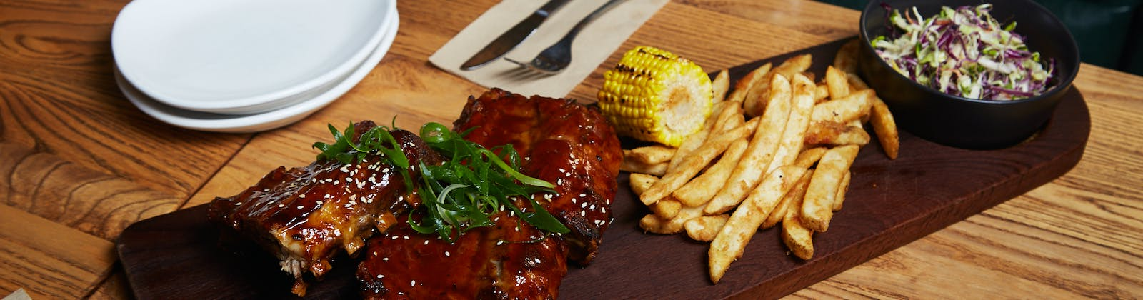 ribs platter with slaw, corn, and fries